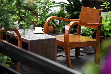 close up white cup and wooden chair in garden